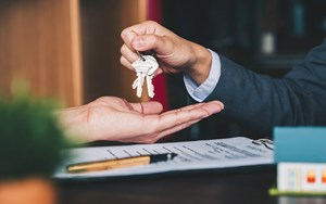 One person hands over keys to another