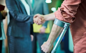 A person on crutches shakes hands with a solicitor