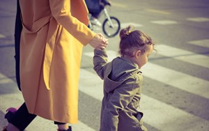 A child holds her mother's hand while crossing the road at a zebra crossing