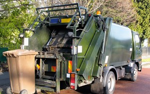 a refuse truck collects a brown bin