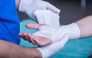 A person has their hand wrapped by a medical professional